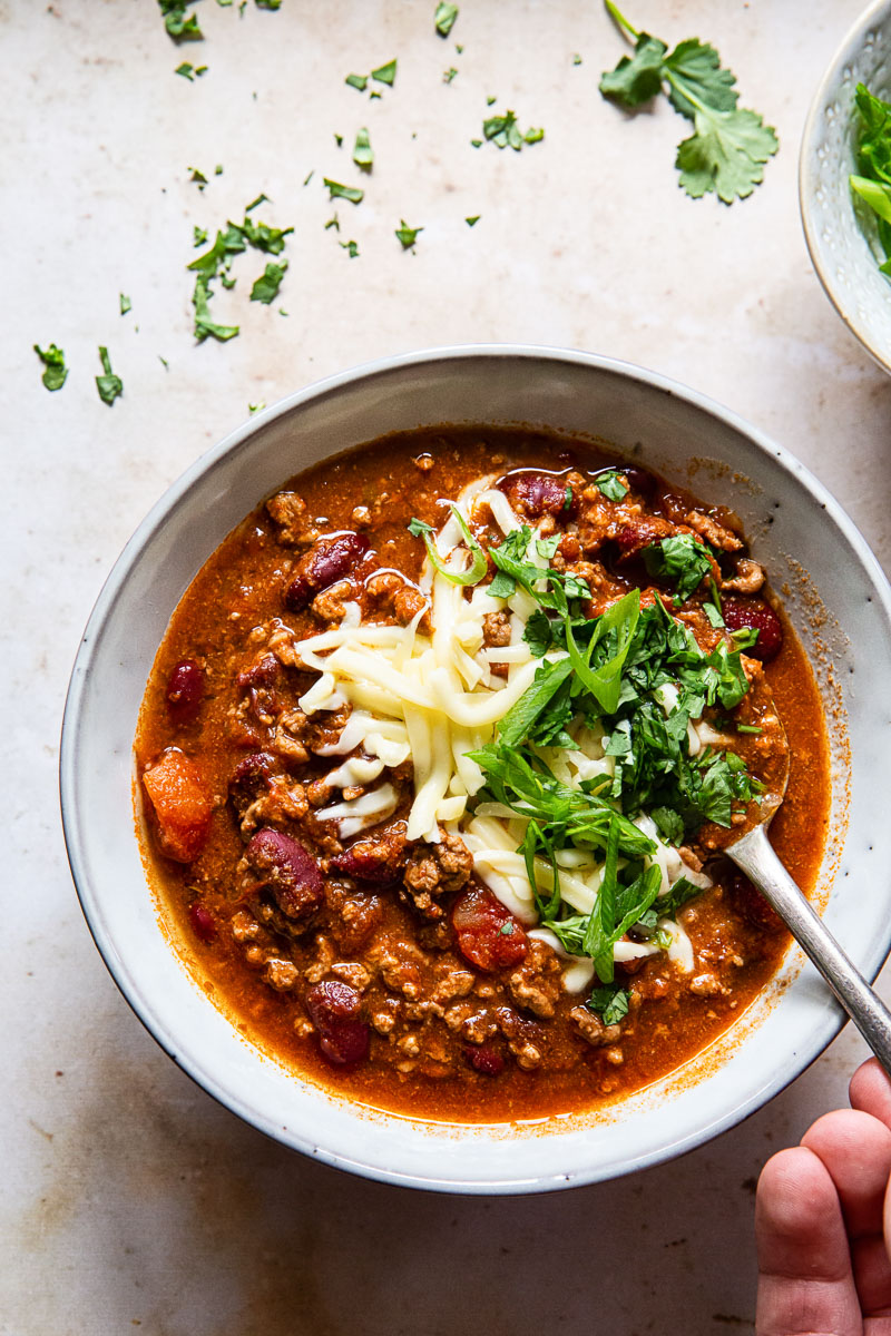 a bowl of chili with a hand holding a spoon dipped in the dish