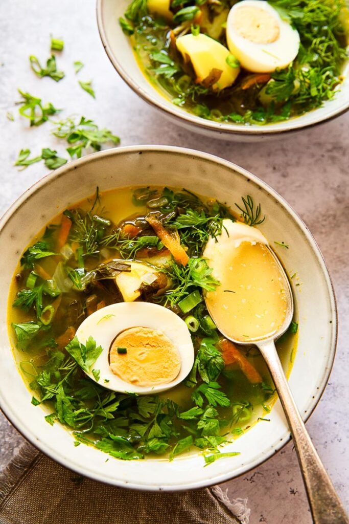 soup topped with greens and a hard boiled egg