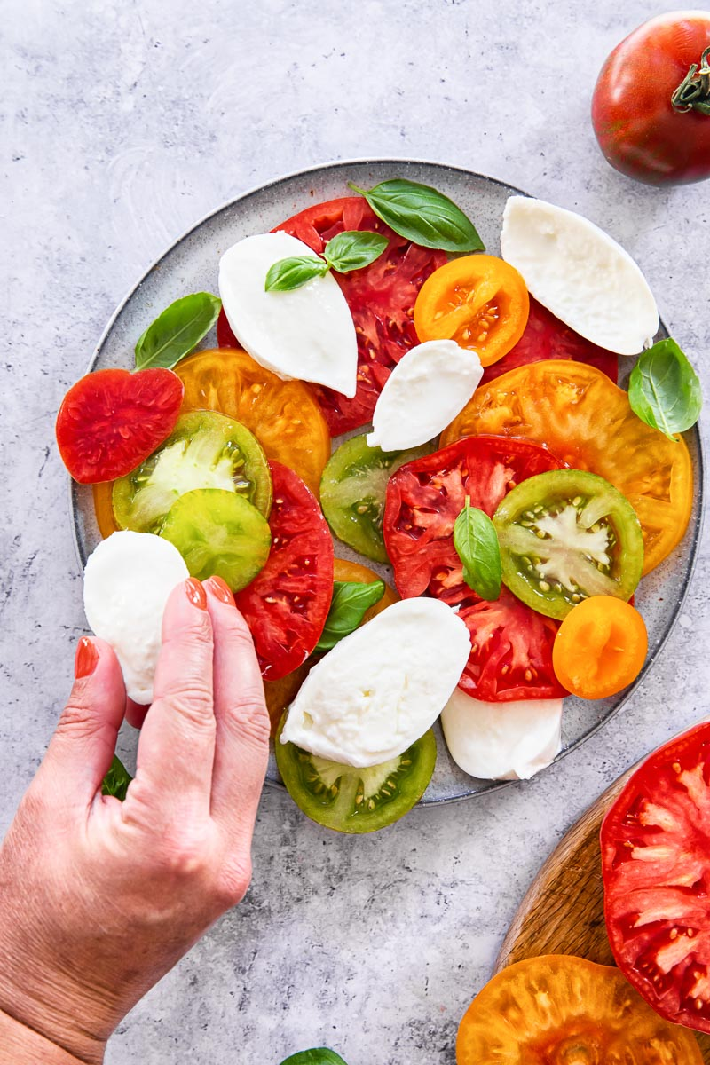 a mozzarella slice is being added to the plate of the Caprese salad