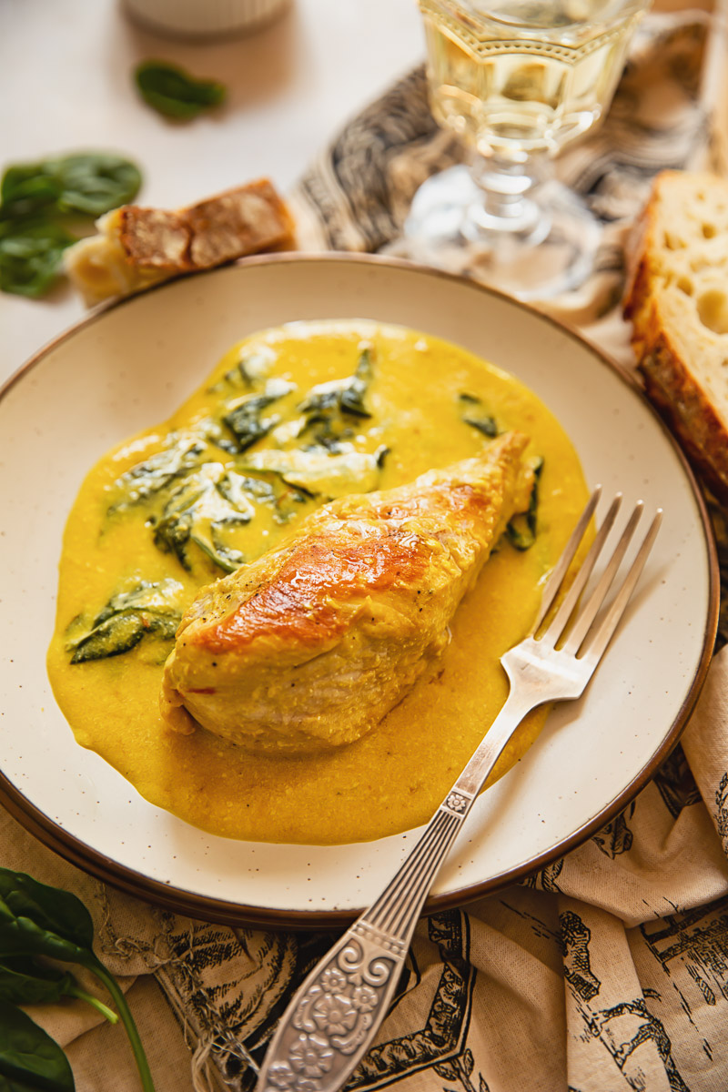 chicken breast with yellow cream sauce and spinach on beige plate, fork and glass of white wine