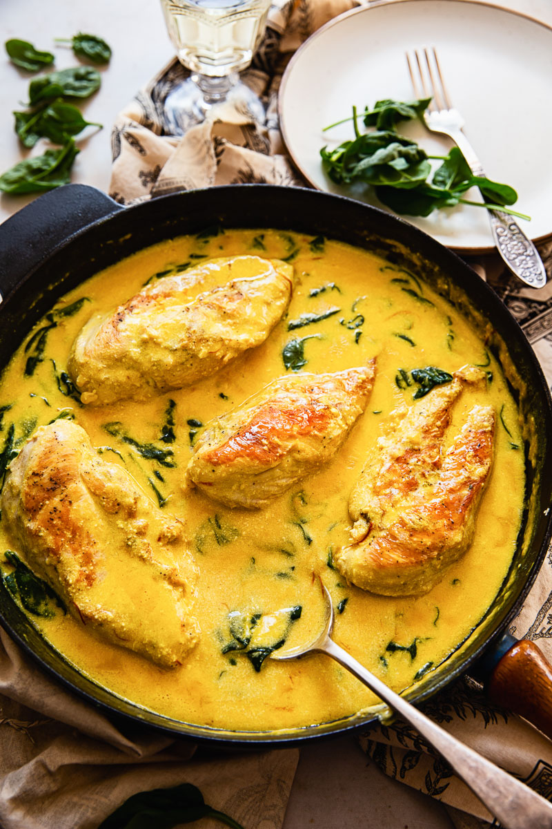 top down view of chicken breasts in cream sauce with spinach in black pan