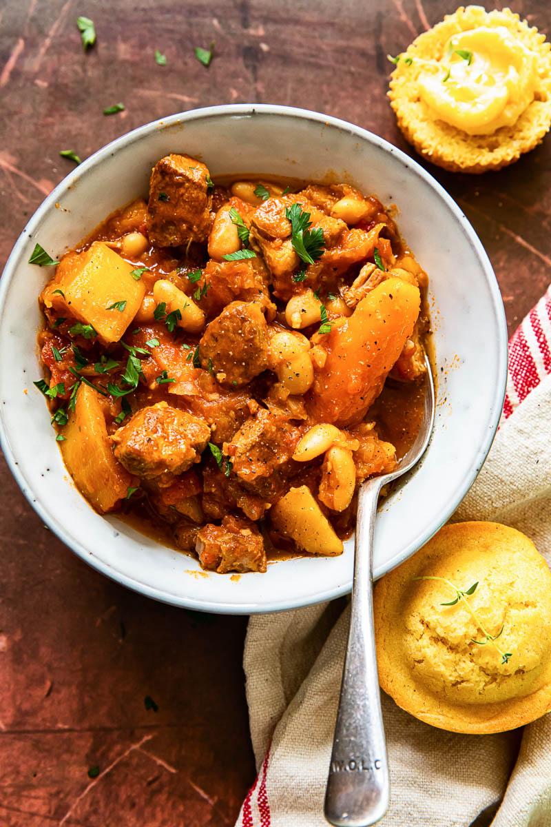 pork stew with carrots and butternut squash in bowl, cornbread muffins