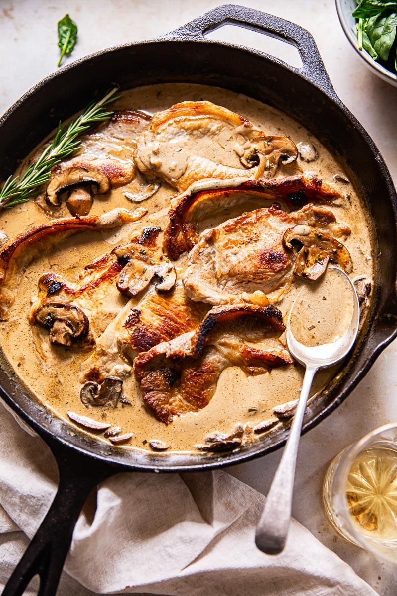 pork loin steaks in creamy sauce with mushrooms in black pan