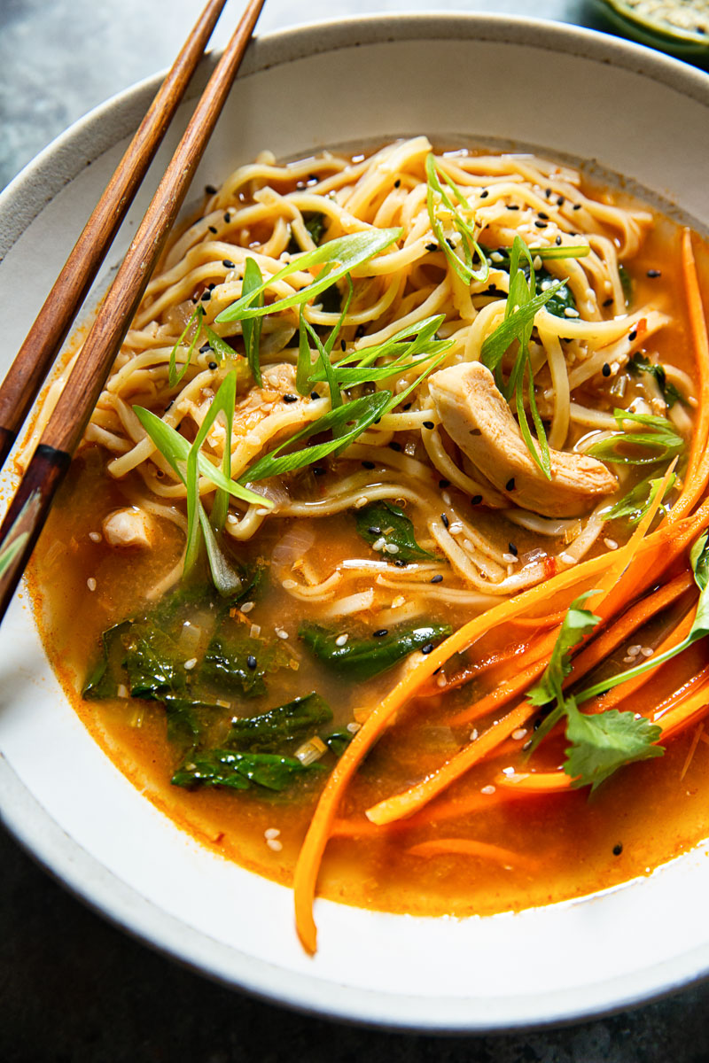 close up image of noodles in broth with chicken, carrots and green onions
