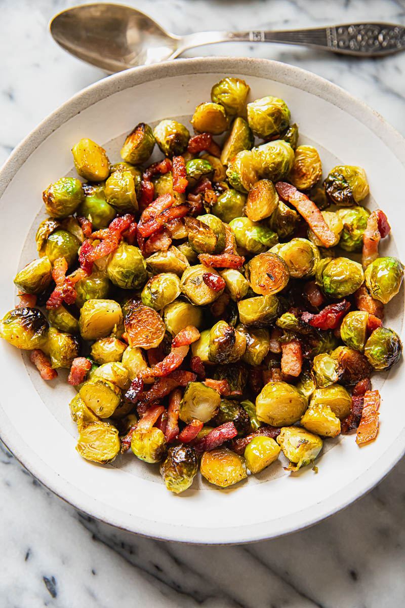 Brussels sprouts with bacon in a cream bowl on marble background