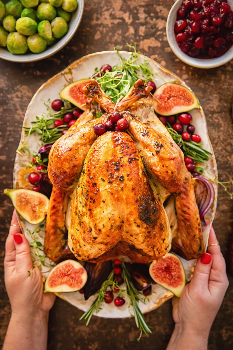 roast turkey garnishes with figs, herbs and cranberries