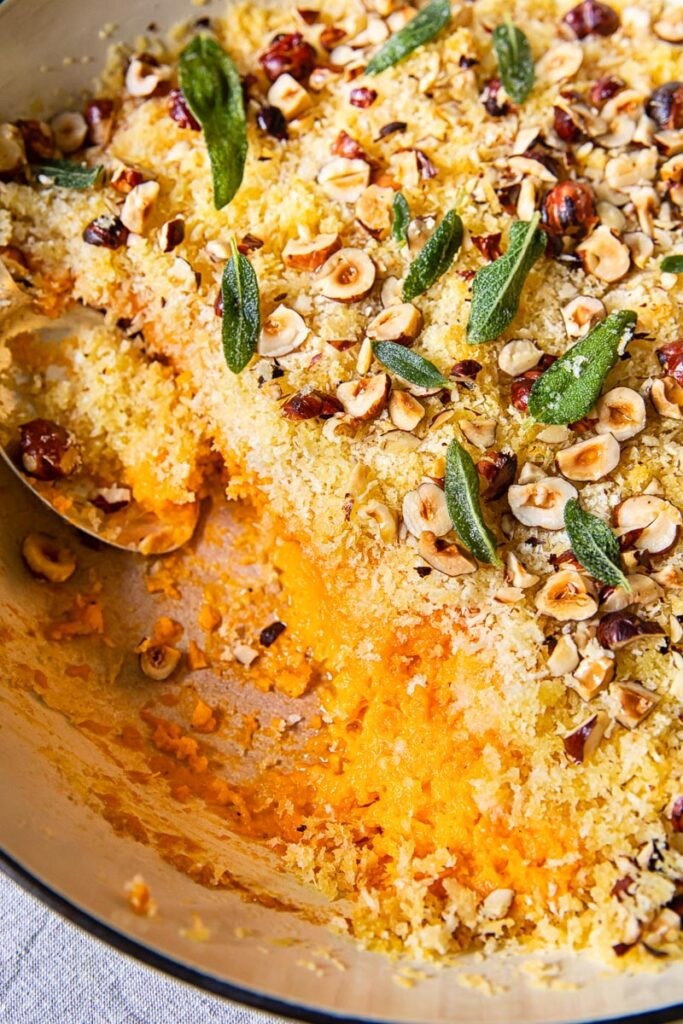 top down view of sweet potato casserole with breadcrumbs, hazelnuts and sage leaves