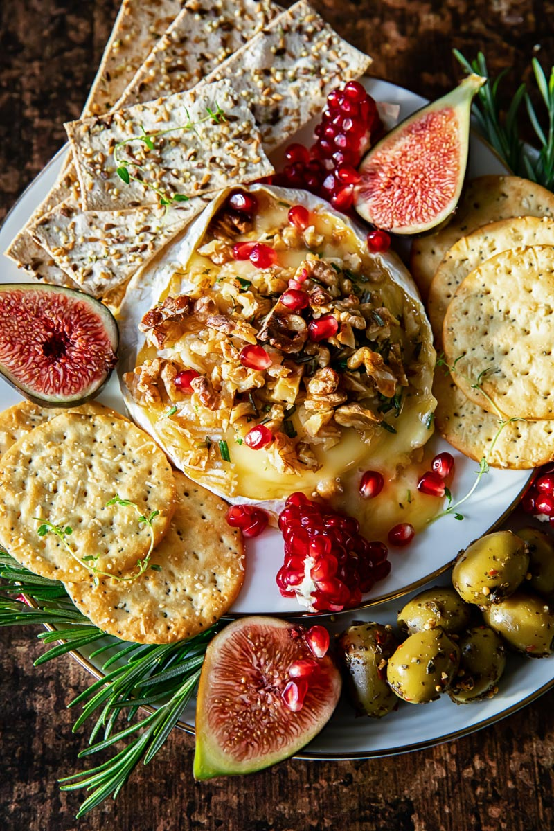 brie cheese topped with walnuts and pomegranate seed, surrounded by crackers, fresh figs and olives