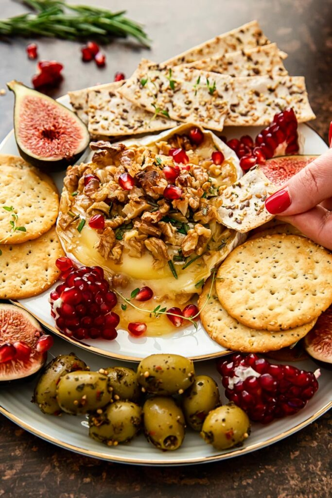 baked brie topped with walnuts and pomegranate seeds, crackers, figs and olives around the plate.