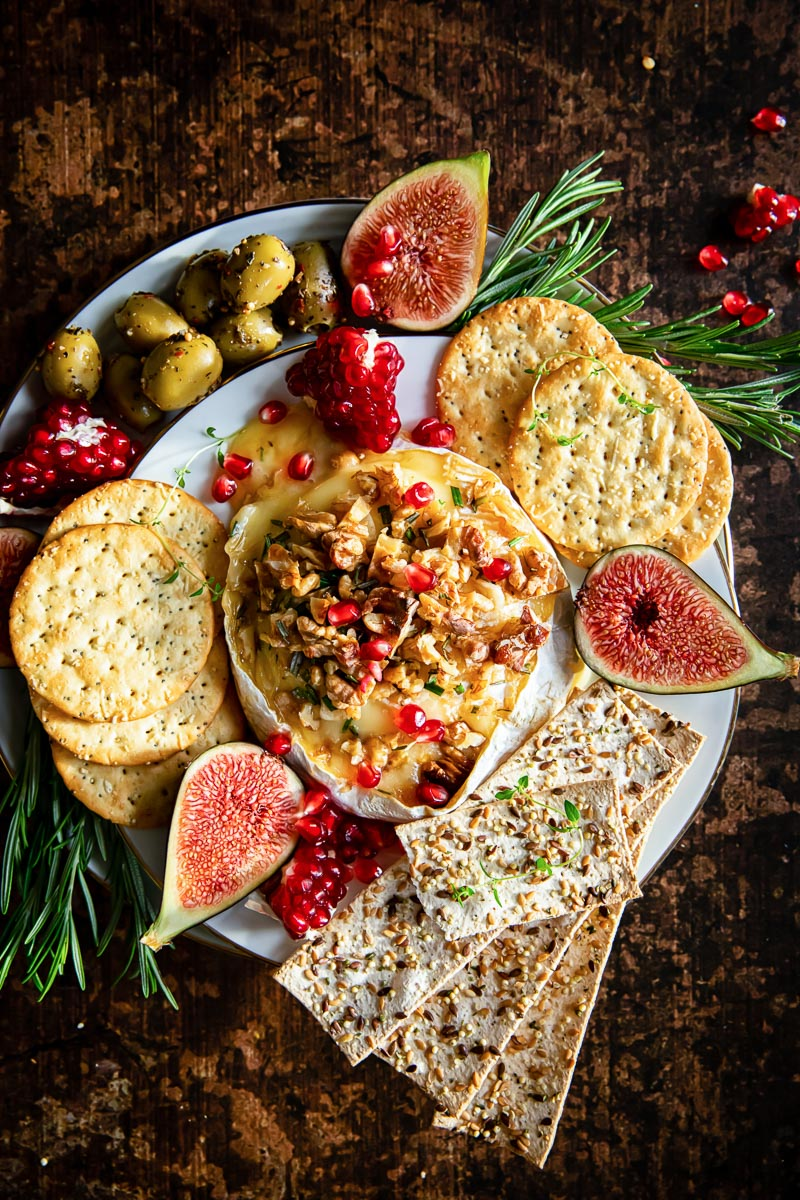 top down view of baked brie surrounded by crackers, olives, figs and pomegranate seeds