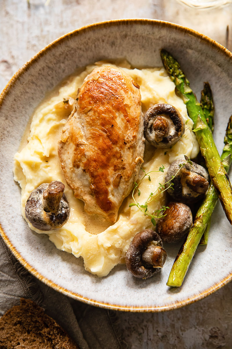 chicken breast and mushrooms on top of mashed potatoes and asparagus on the side