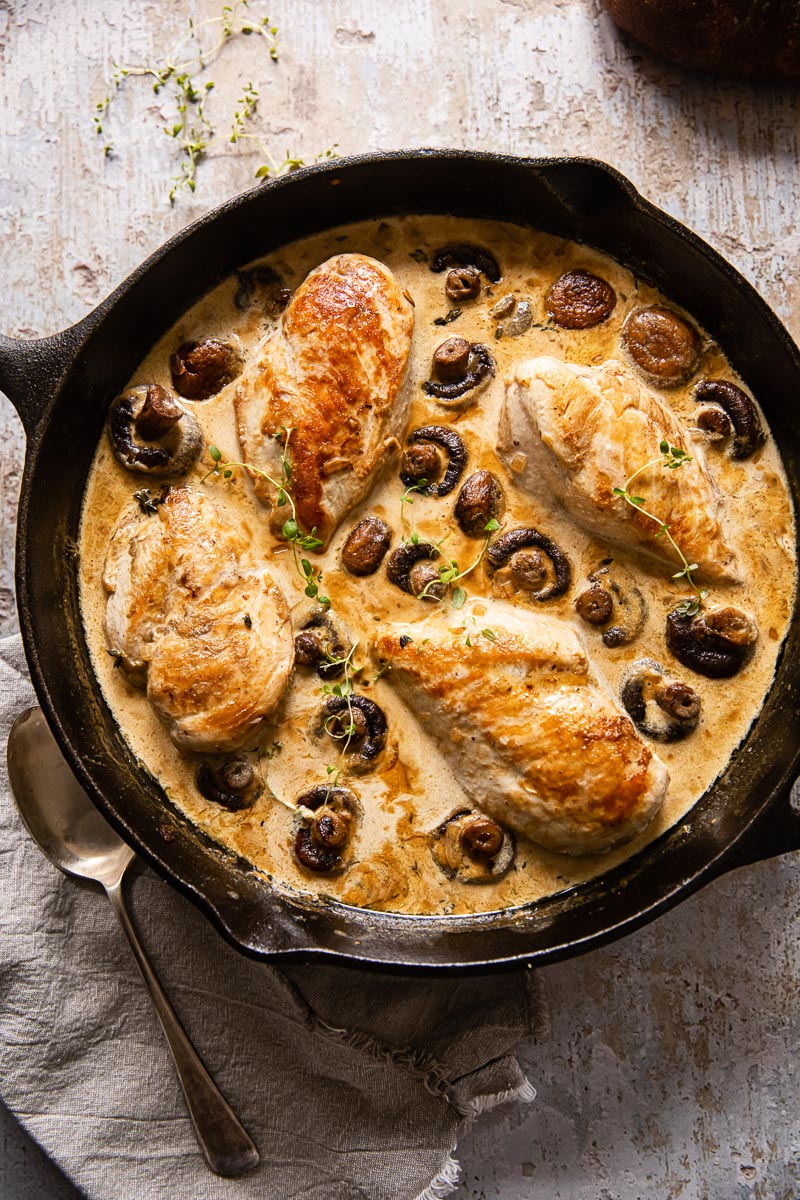top down view of chicken supreme with mushrooms in cream sauce in cast iron skillet