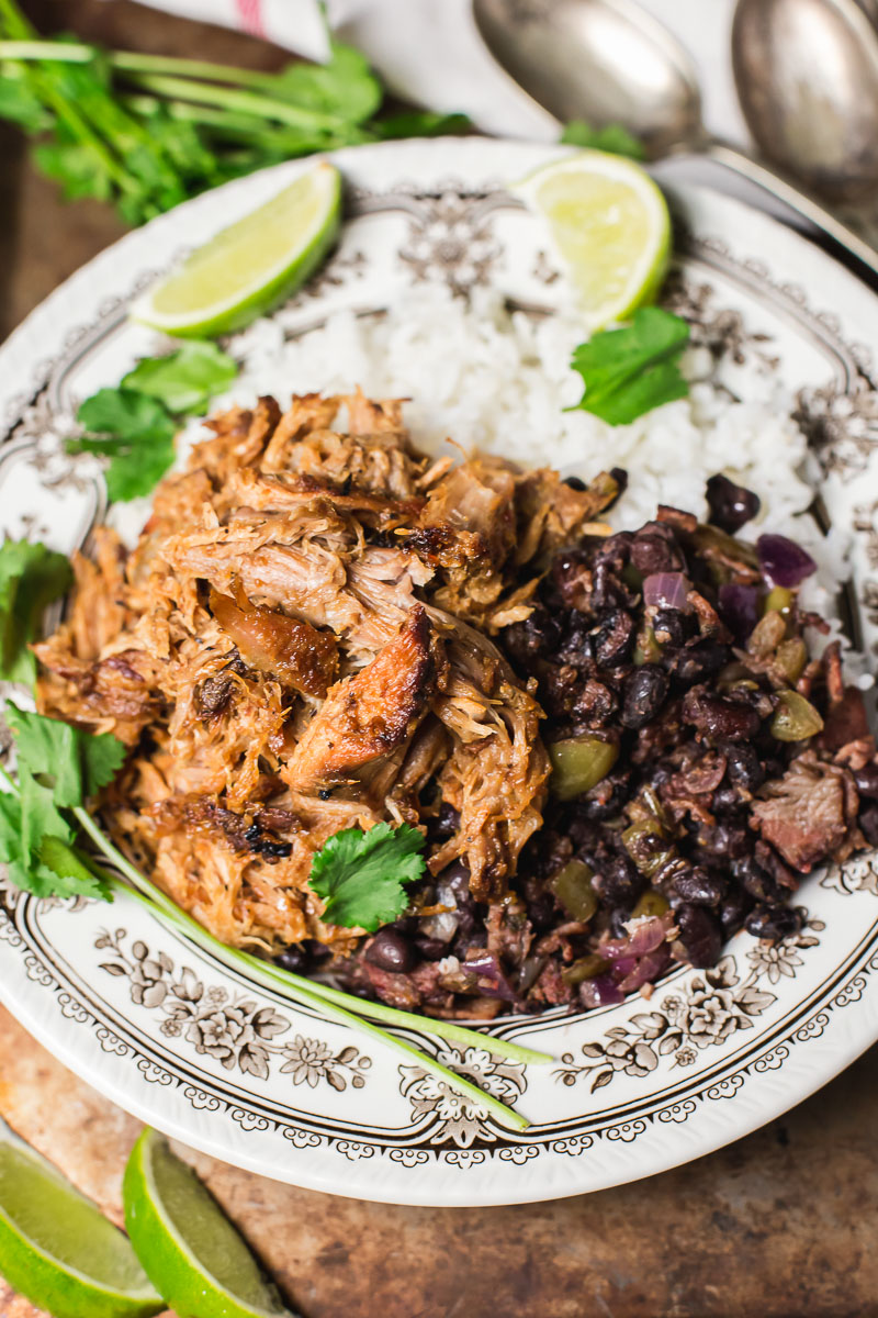Cuban style pork and black bean on top of white rice, two slices of lime.
