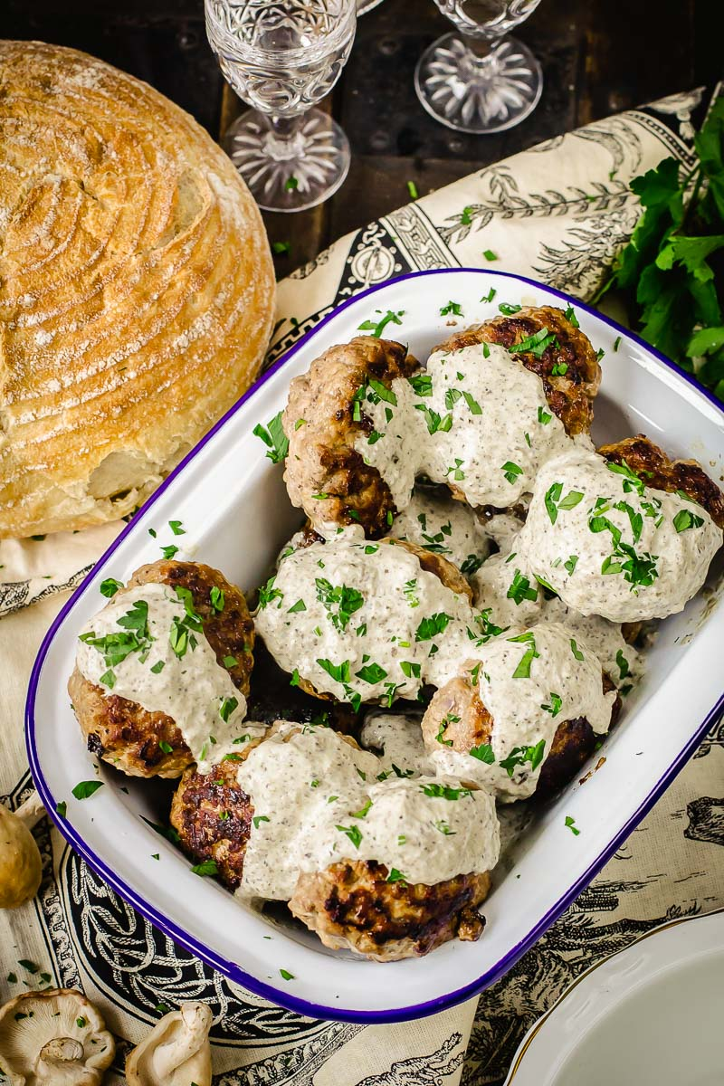 meat patties with mushroom sauce poured over them and sprinkled with fresh herbs