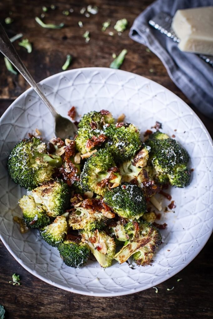 roasted broccoli with sun-dried tomatoes in grey bowl