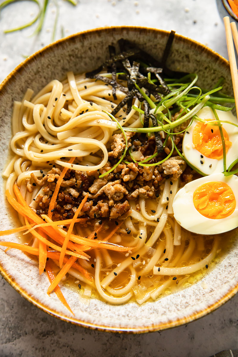 noodle soup topped with boiled egg, matchstick carrots and green onions
