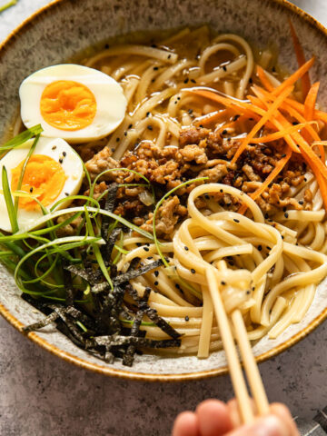 udon noodle soup topped with ground pork, boiled egg, green onion and carrots