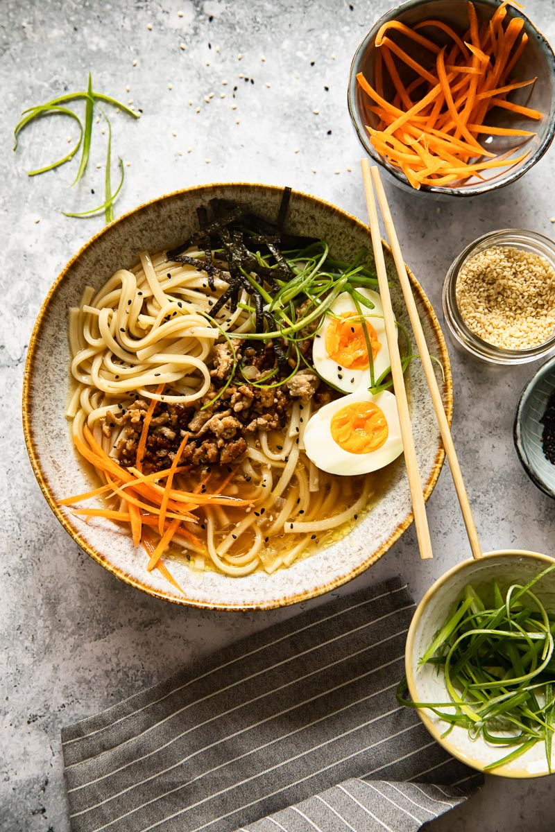 Japanese noodle soup in a bowl with various toppings around it in small bowls