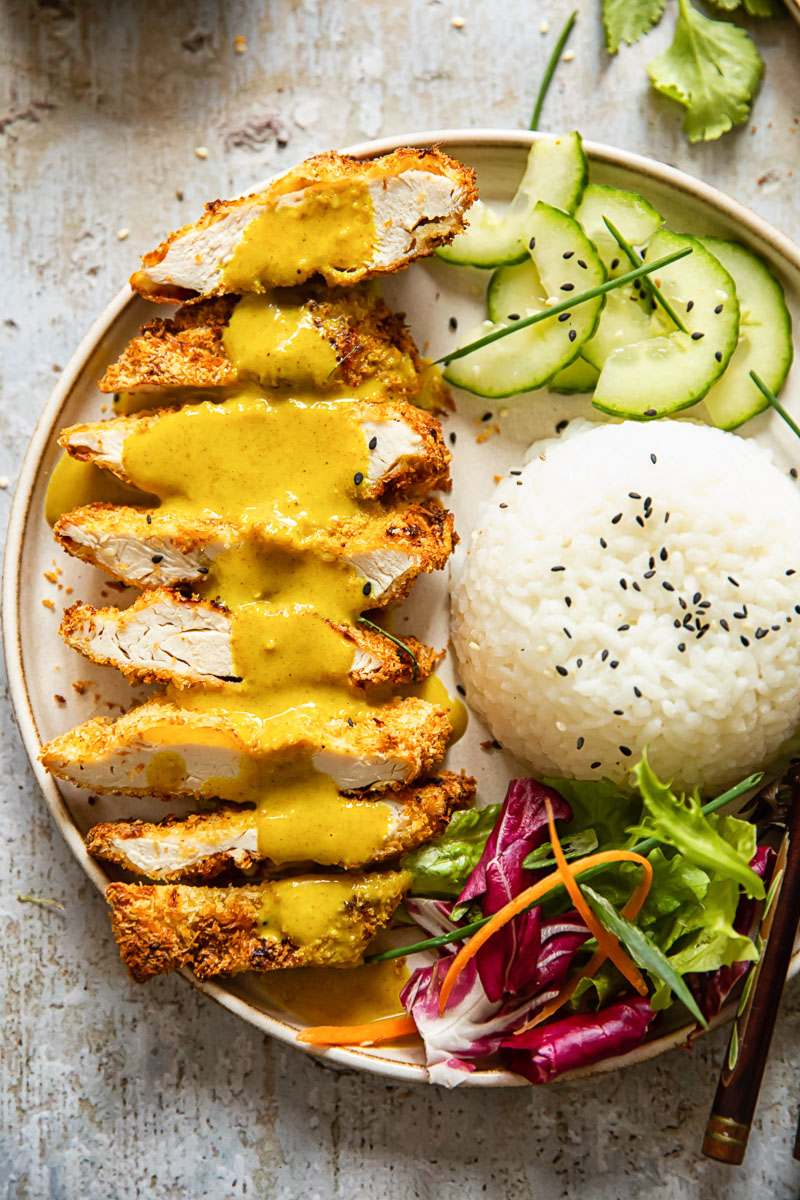 chicken katsu with curry poured over, rice, sliced cucumber