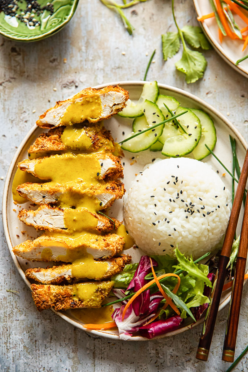 top down view of a plate with chicken Katsu curry, rice, sliced cucumber and salad