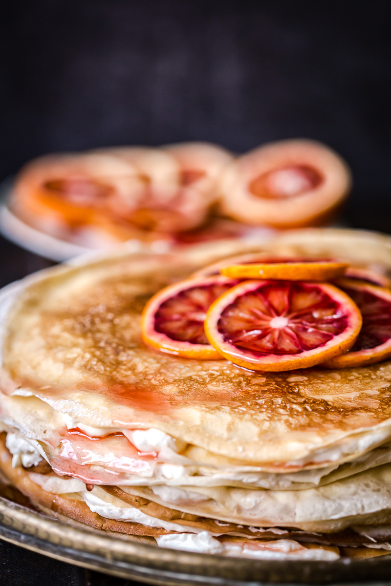 crepe cake topped with sliced blood oranges