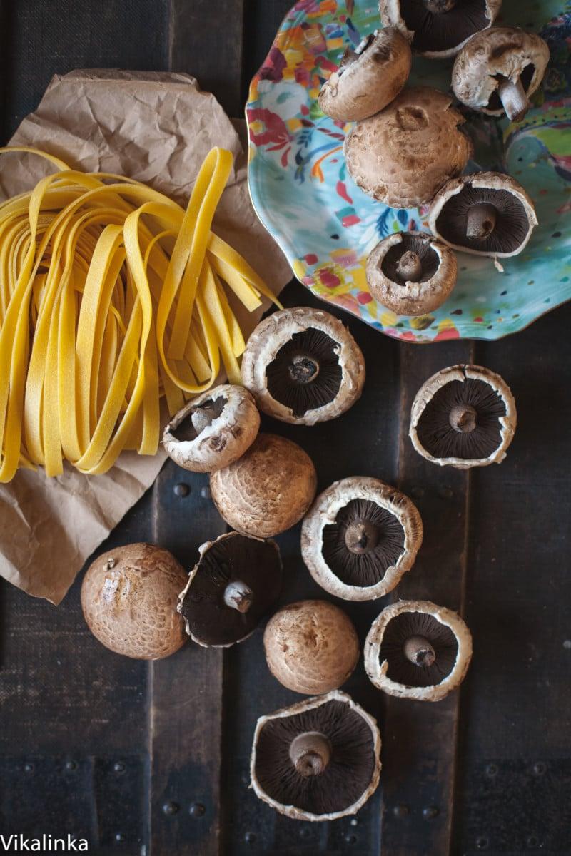 fresh tagliatelle and portobello mushrooms on dark background