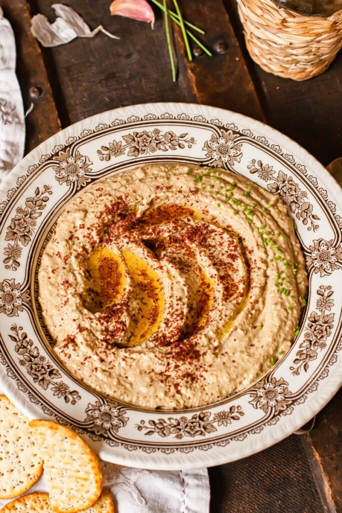 baba ganoush in a bowl sprinkled with sumac and chives on brown background.