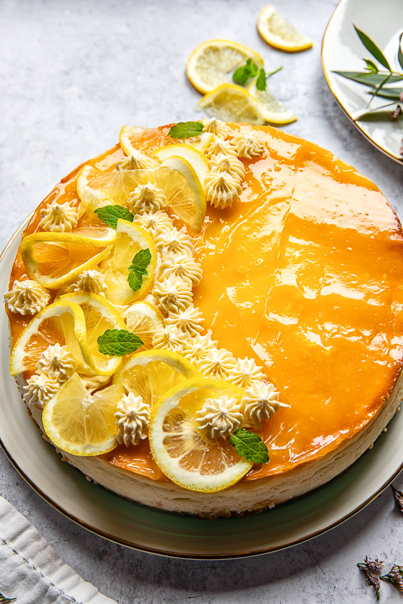lemon cheesecake decorated with lemon slices and whipped cream rosettes