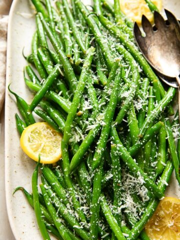 green beans topped with Parmesan and slices of lemon on a platter