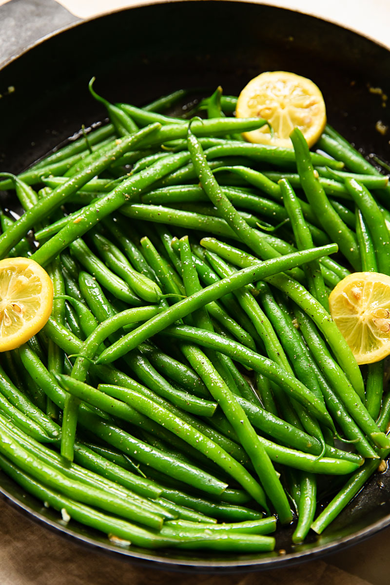 green beans with lemon slices in a cast iron pan