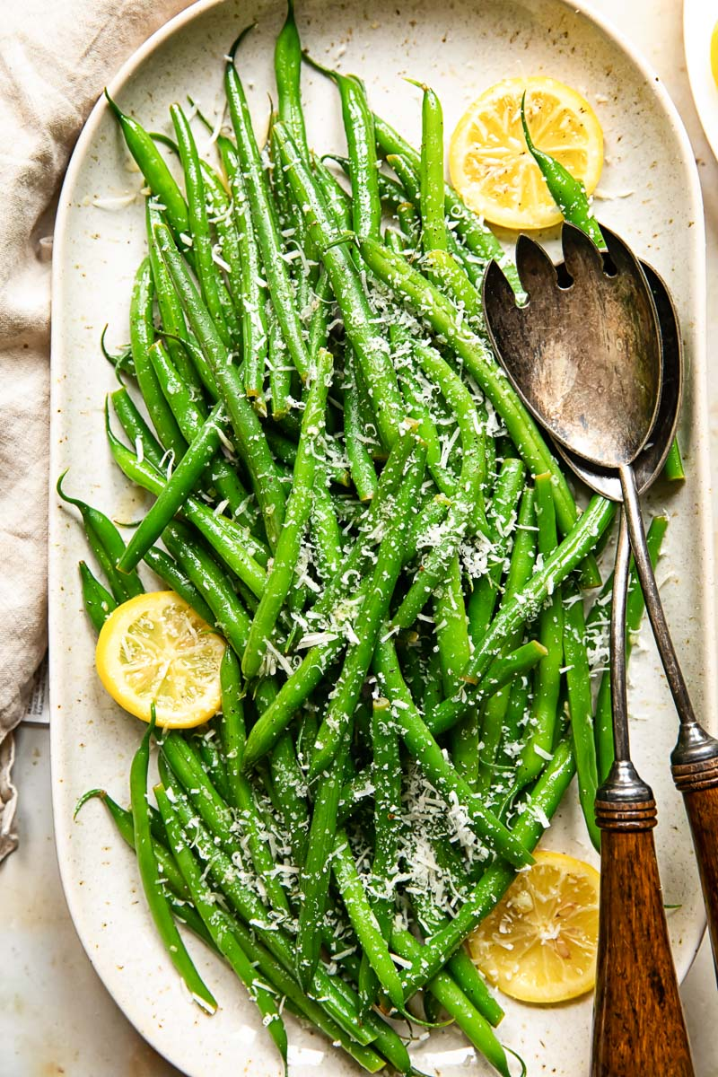 top down view of green beans with lemon slices and Parmesan