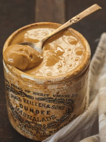 peanut butter in a brown jar with a spoon in it