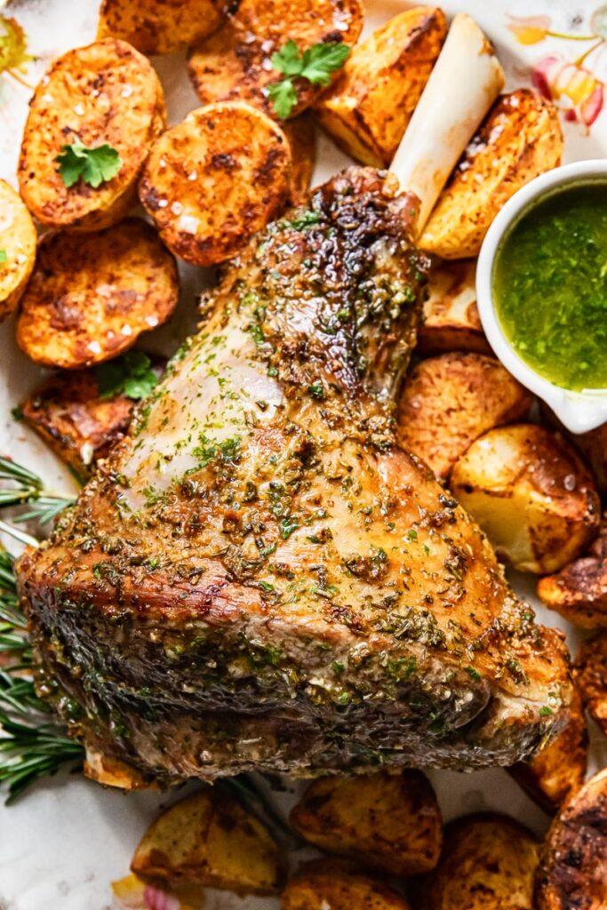top down view of roast leg of lamb, mint sauce and roast potatoes