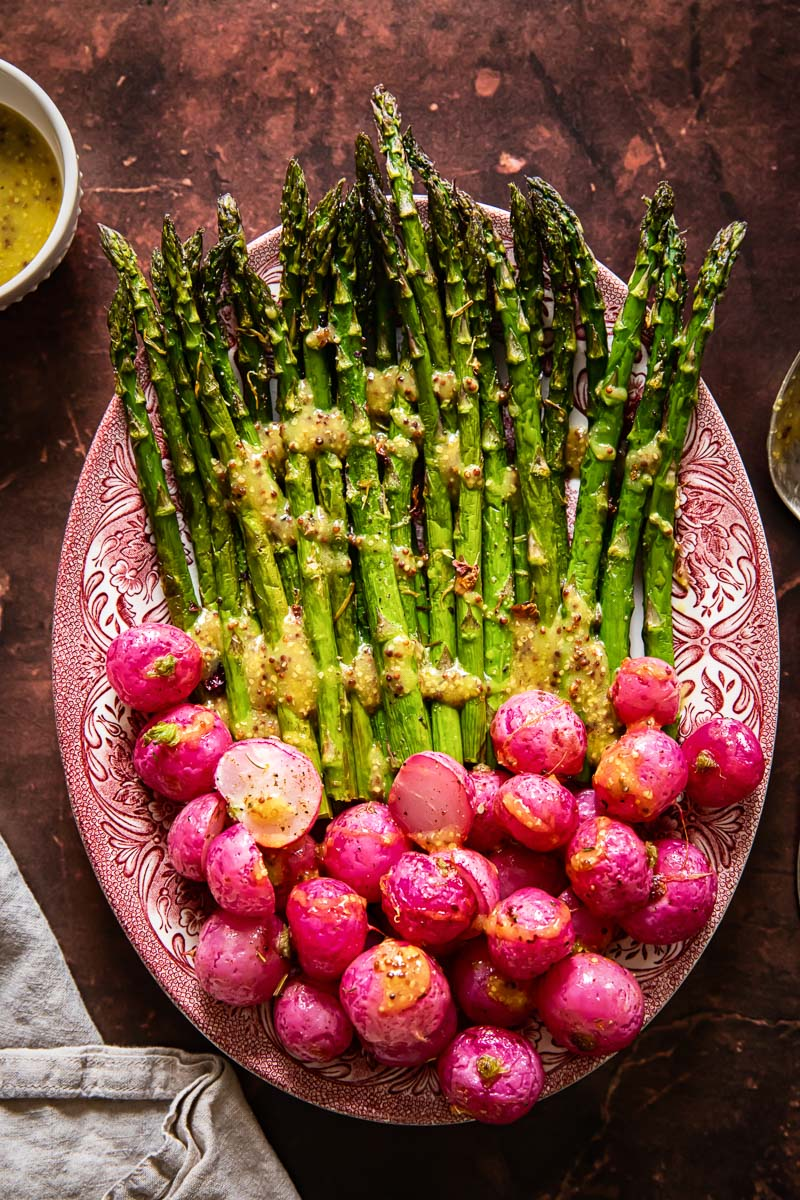 top down view on roasted asparagus and radishes with vinaigrette drizzled over.