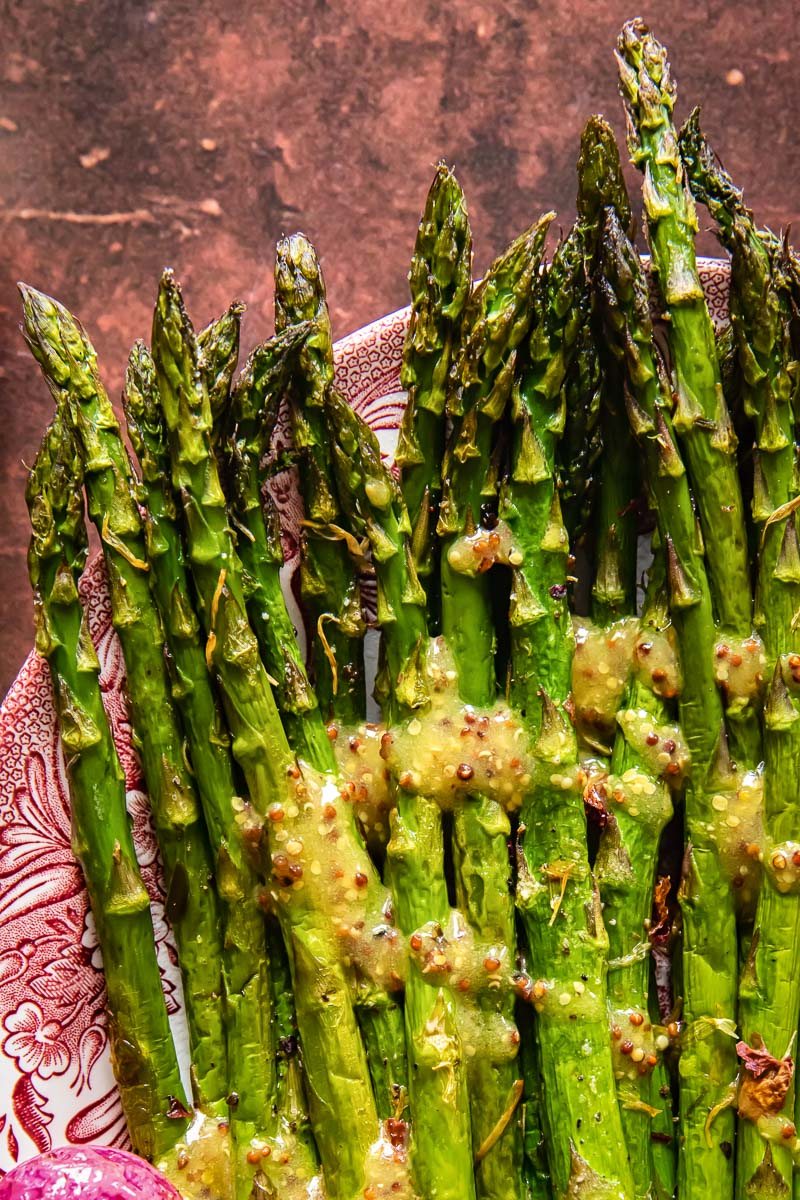 top down view of roasted asparagus with mustard vinaigrette on a platter