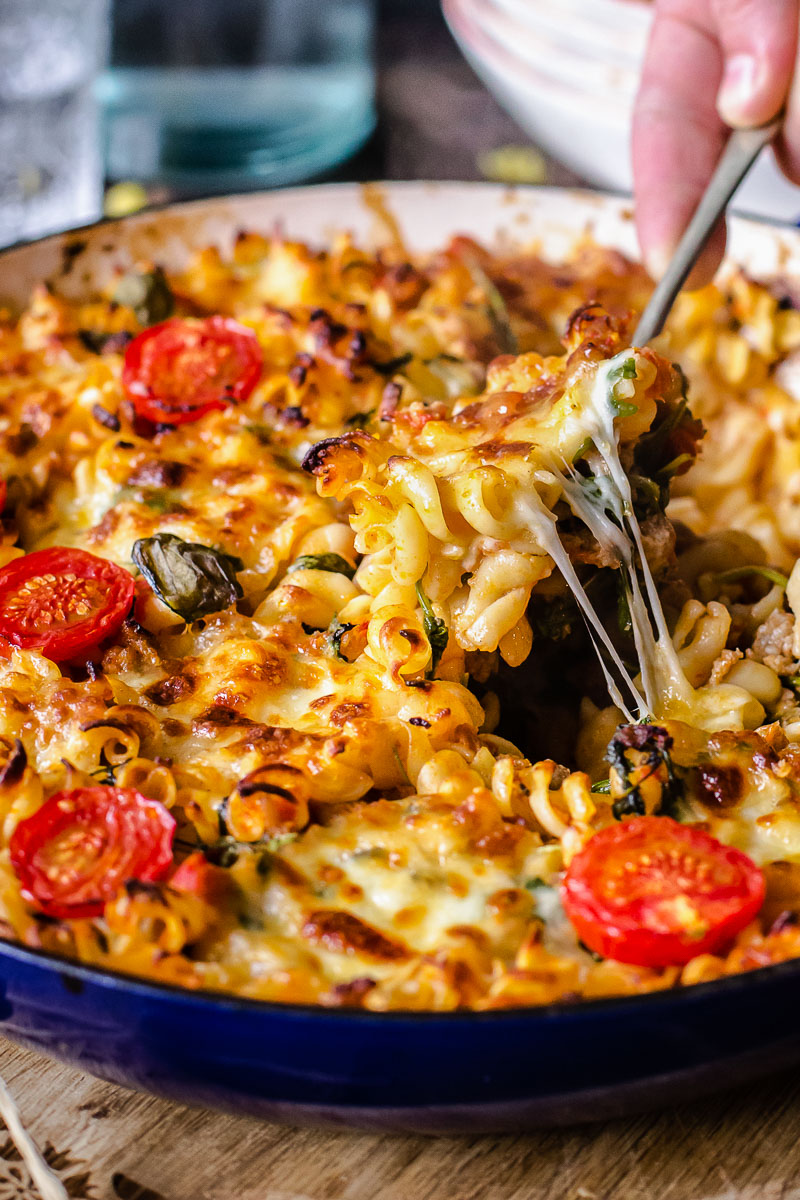 side view of sausage pasta casserole with a hand holding a spoon