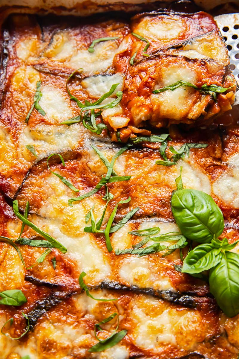 close up of eggplant parmigiana with a slice being lifted out of the pan