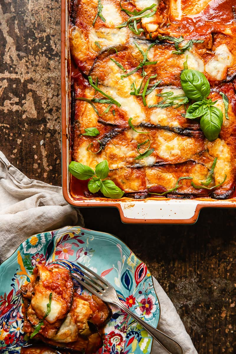 top down view of aubergine parmigiana in a pan and a portion on a blue plate