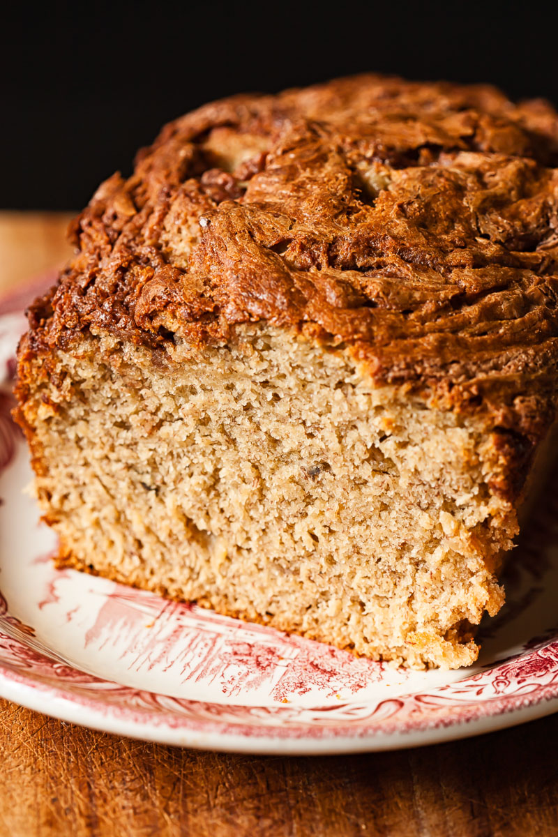 banana bread on a plate with the first slice cut off