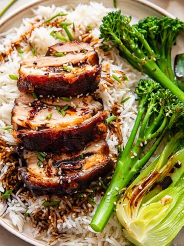 sliced pork belly on top of rice, tenderstem broccoli and bok choy