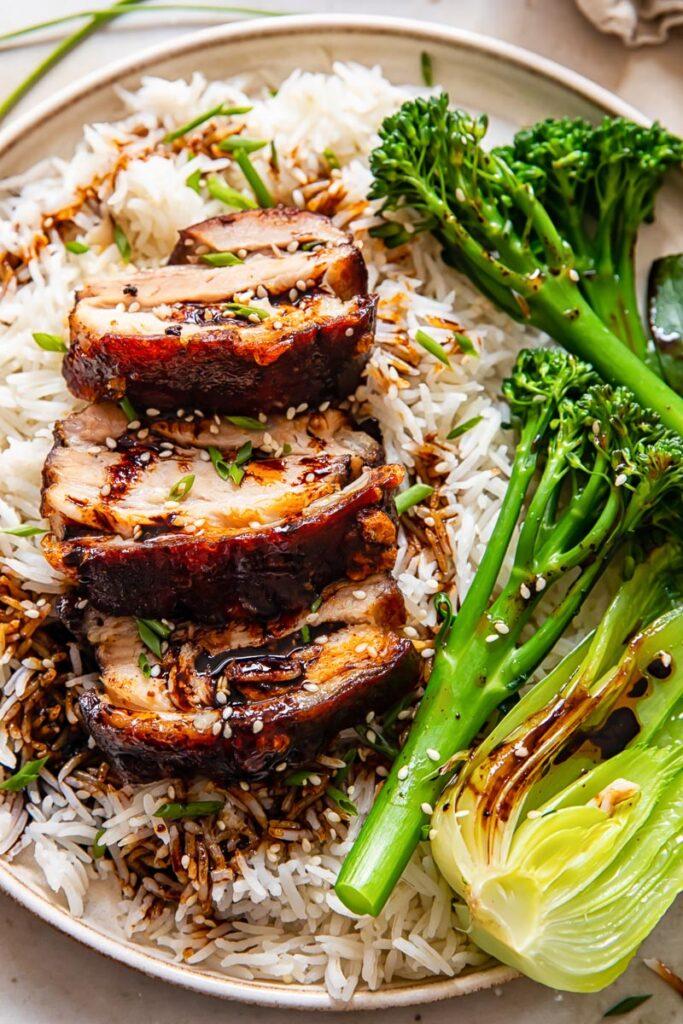 sliced pork belly on top of rice, tenderstem broccoli and bok choy