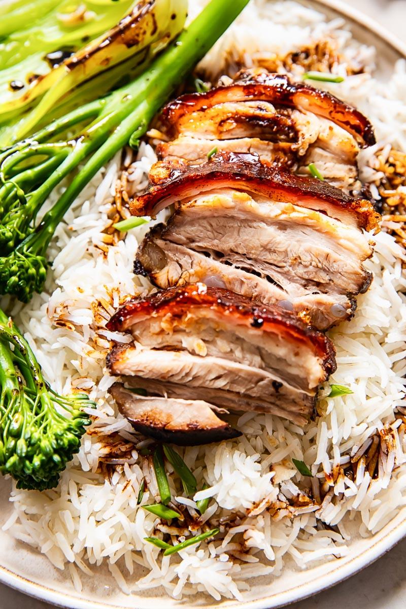 pork sliced on top of rice, broccoli on a plate