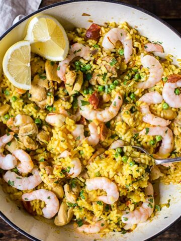 top down view of yellow Spanish rice with chicken, shrimp and lemon slices