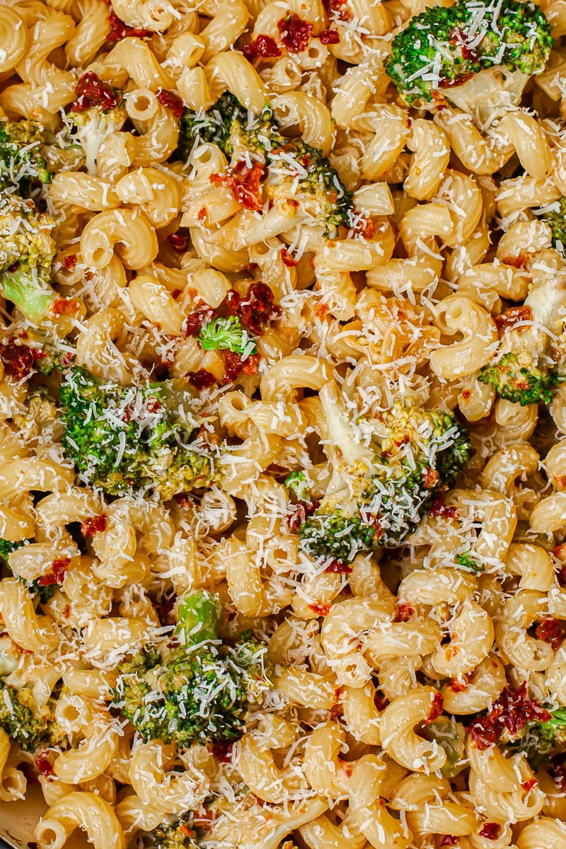 top down view of pasta dish with broccoli and sun-dried tomatoes sprinkled with Parmesan cheese