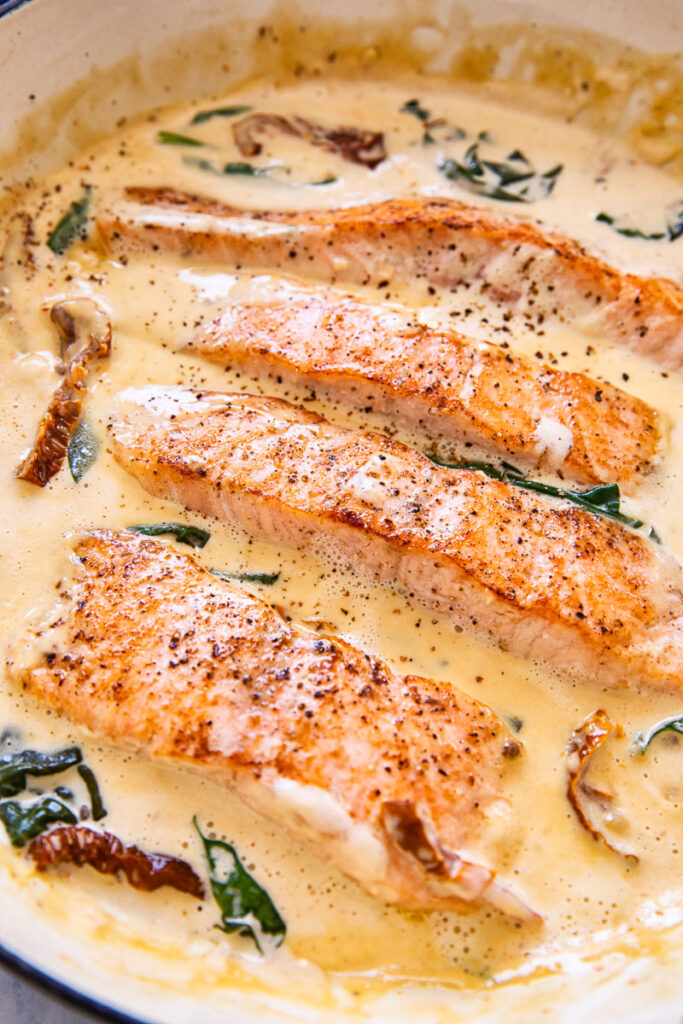 salmon in cream sauce with sun-dried tomatoes and spinach