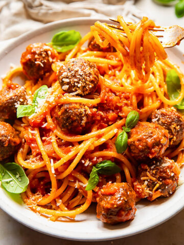 bucatini with meatballs in a cream coloured bowl, topped with fresh basil leaves