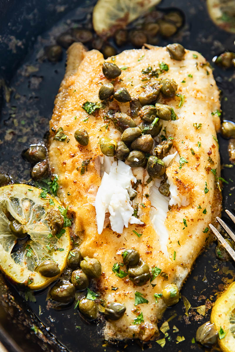 close us of sole topped with capers and lemon sliced in cast iron pan