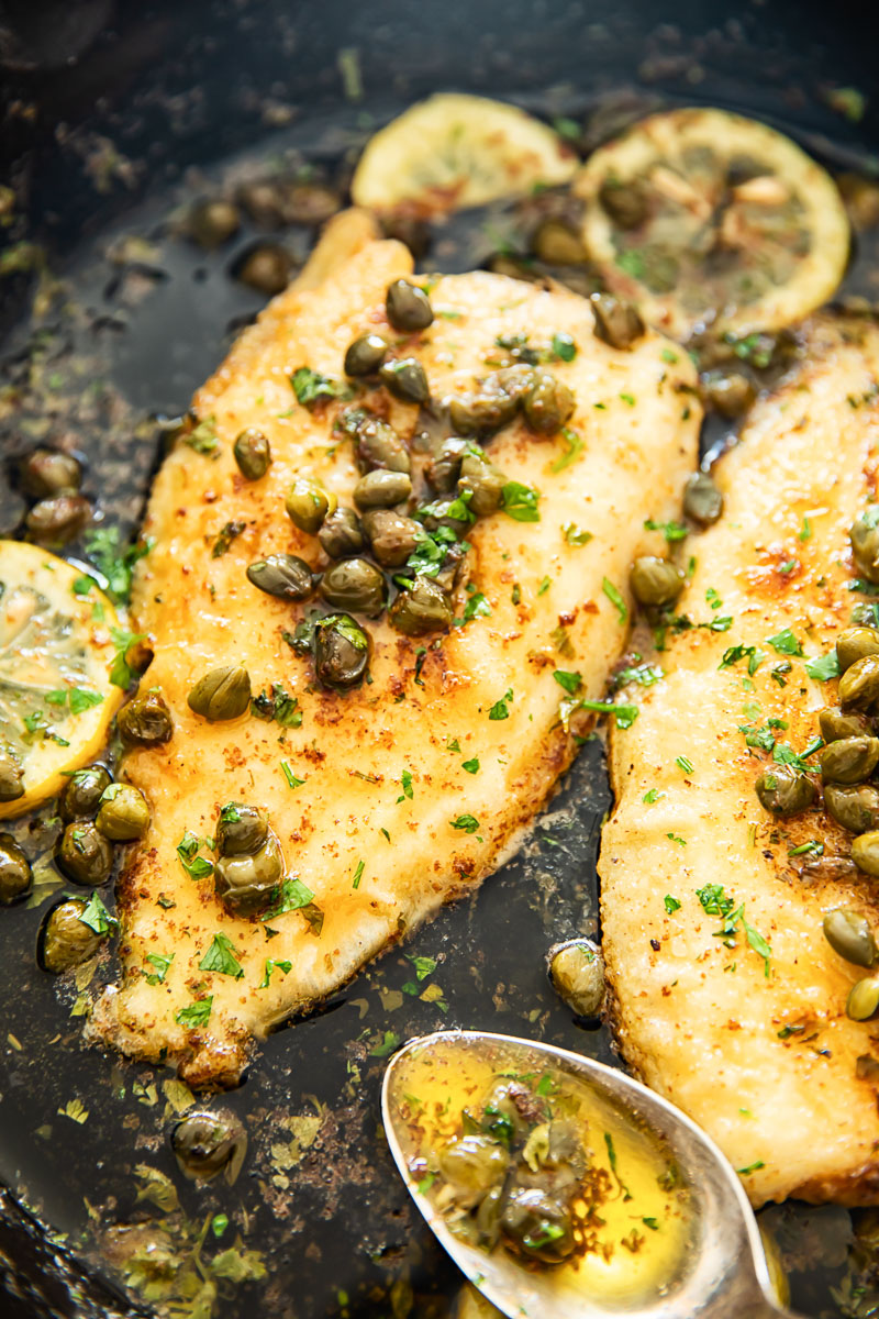 sole fish in lemon butter sauce with capers in cast iron pan