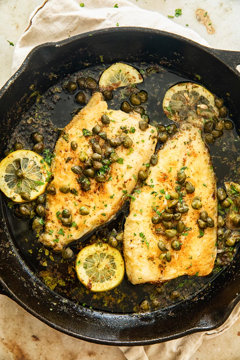 two sole fish topped with capers and lemon slices in cast iron pan
