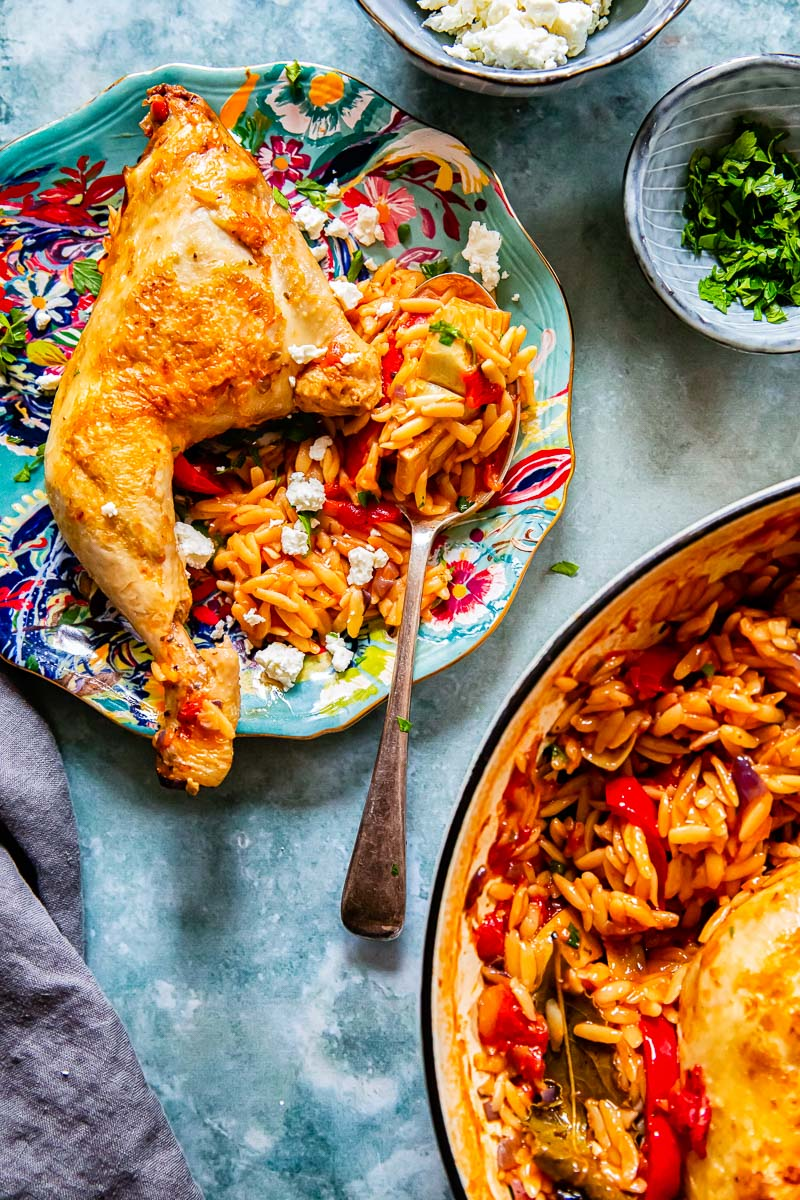 chicken leg and orzo on a blue plate, a pan with orzo, feta and parsley in small bowls.